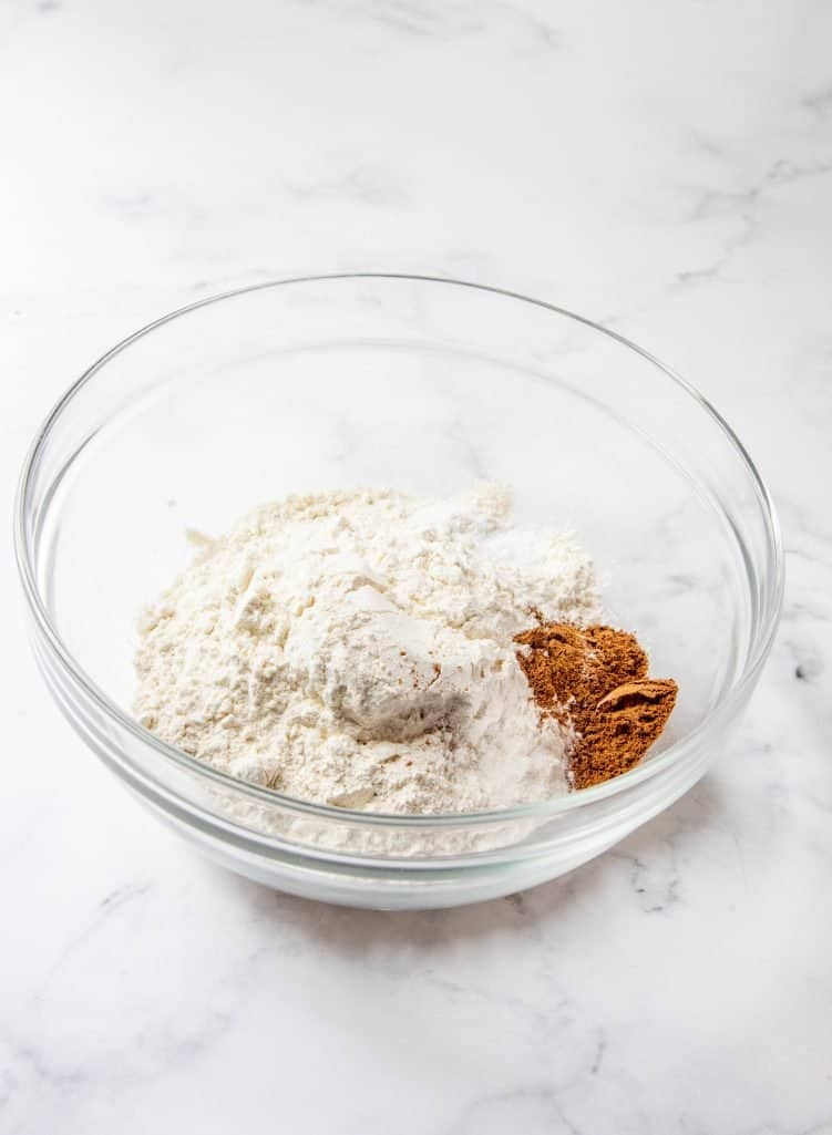 flour and pumpkin pie spice and baking soda added to a clear bowl