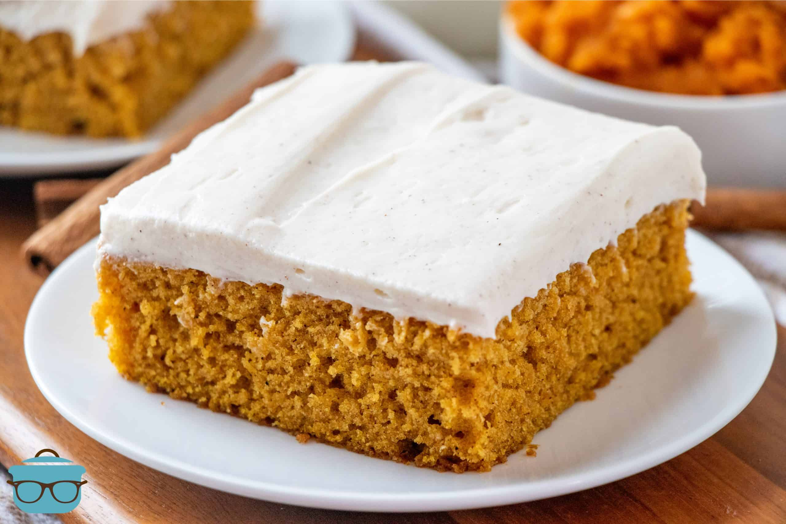Pumpkin cake bar slice on a small white plate with a bowl of pumpkin puree in a bowl in the background.