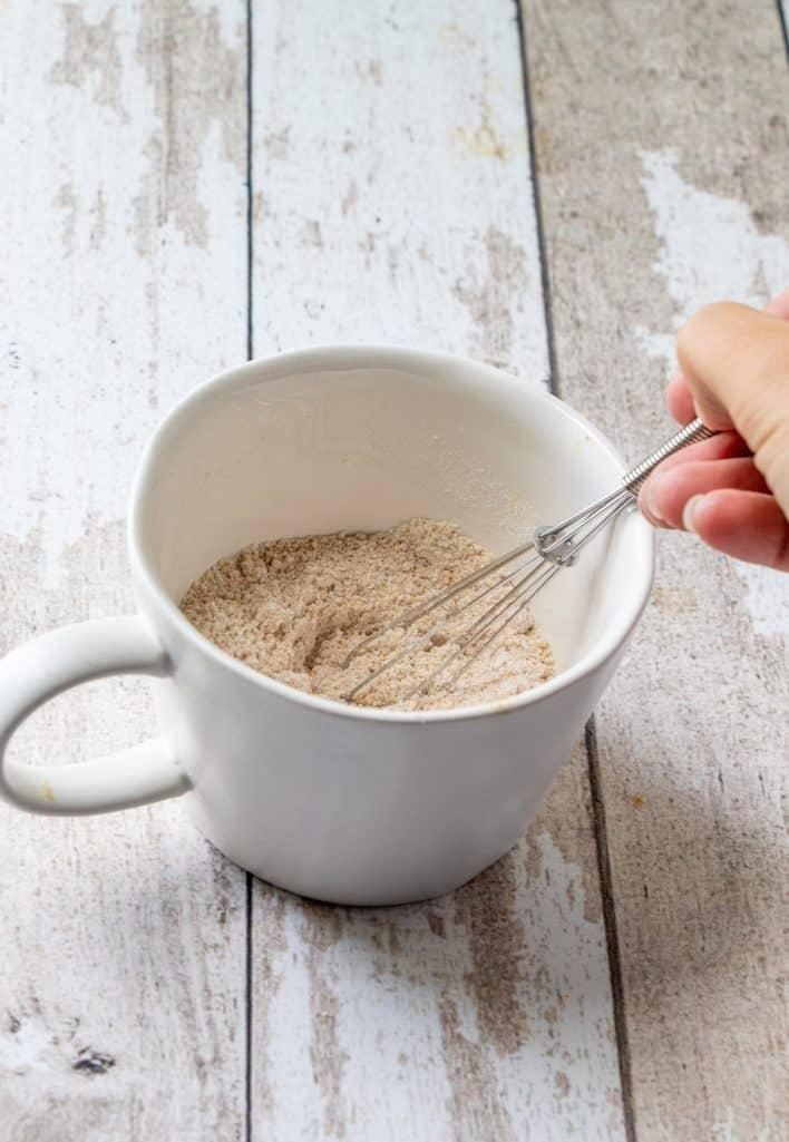 farine, sucre, levure chimique, sel et épices pour tarte à la citrouille battus ensemble dans une tasse blanche