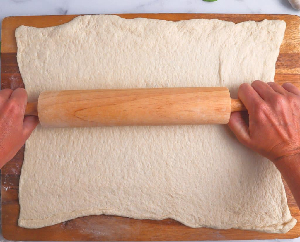 rolling out pizza dough with a rolling pin