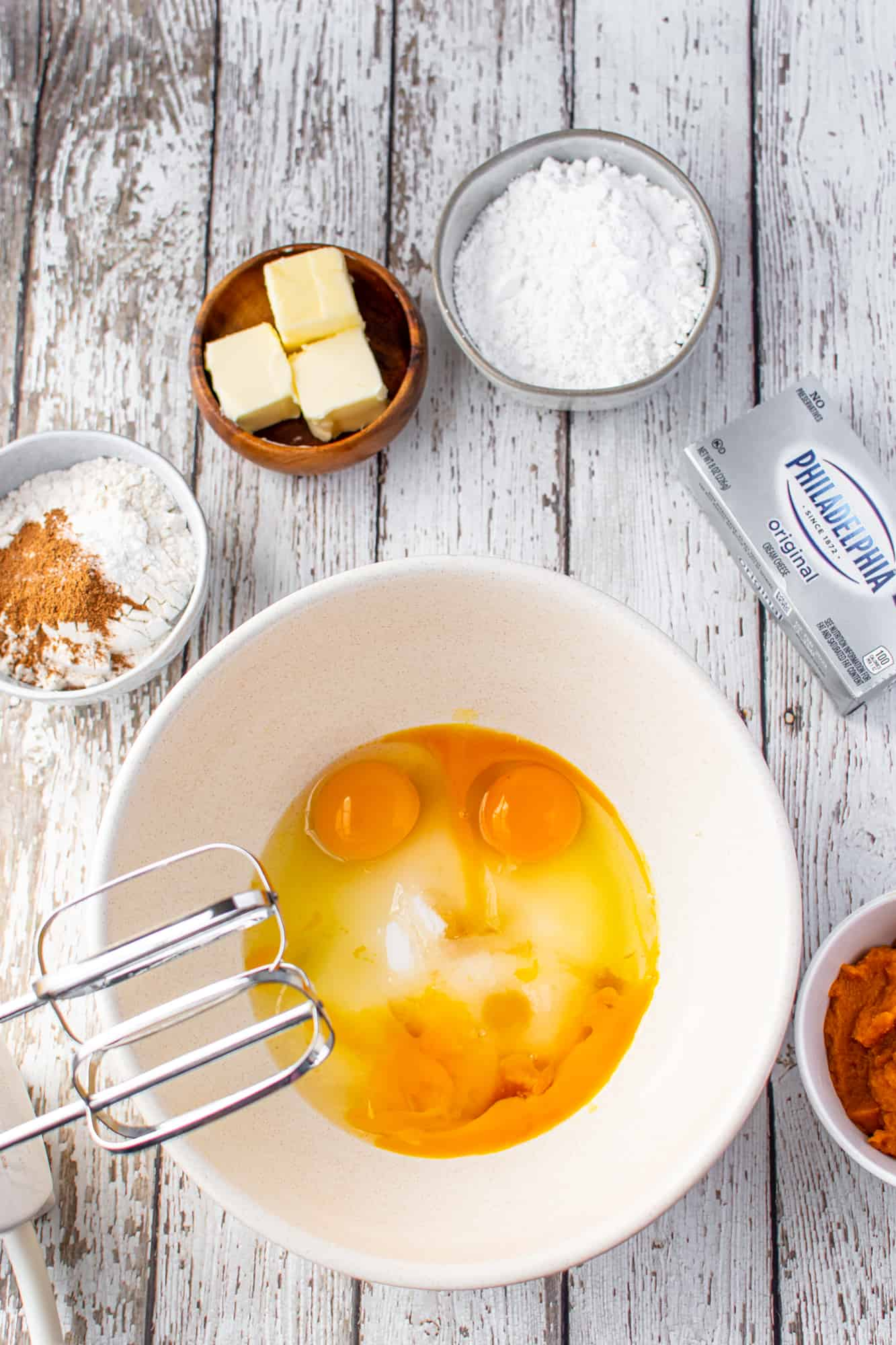 sugar and eggs in a white bowl with an electric mixer on the side.