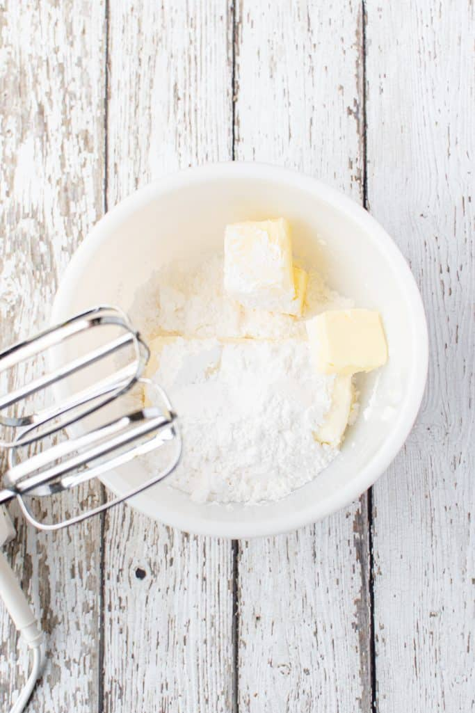 softened cream cheese and softened butter mixed together with an electric mixer in a white bowl