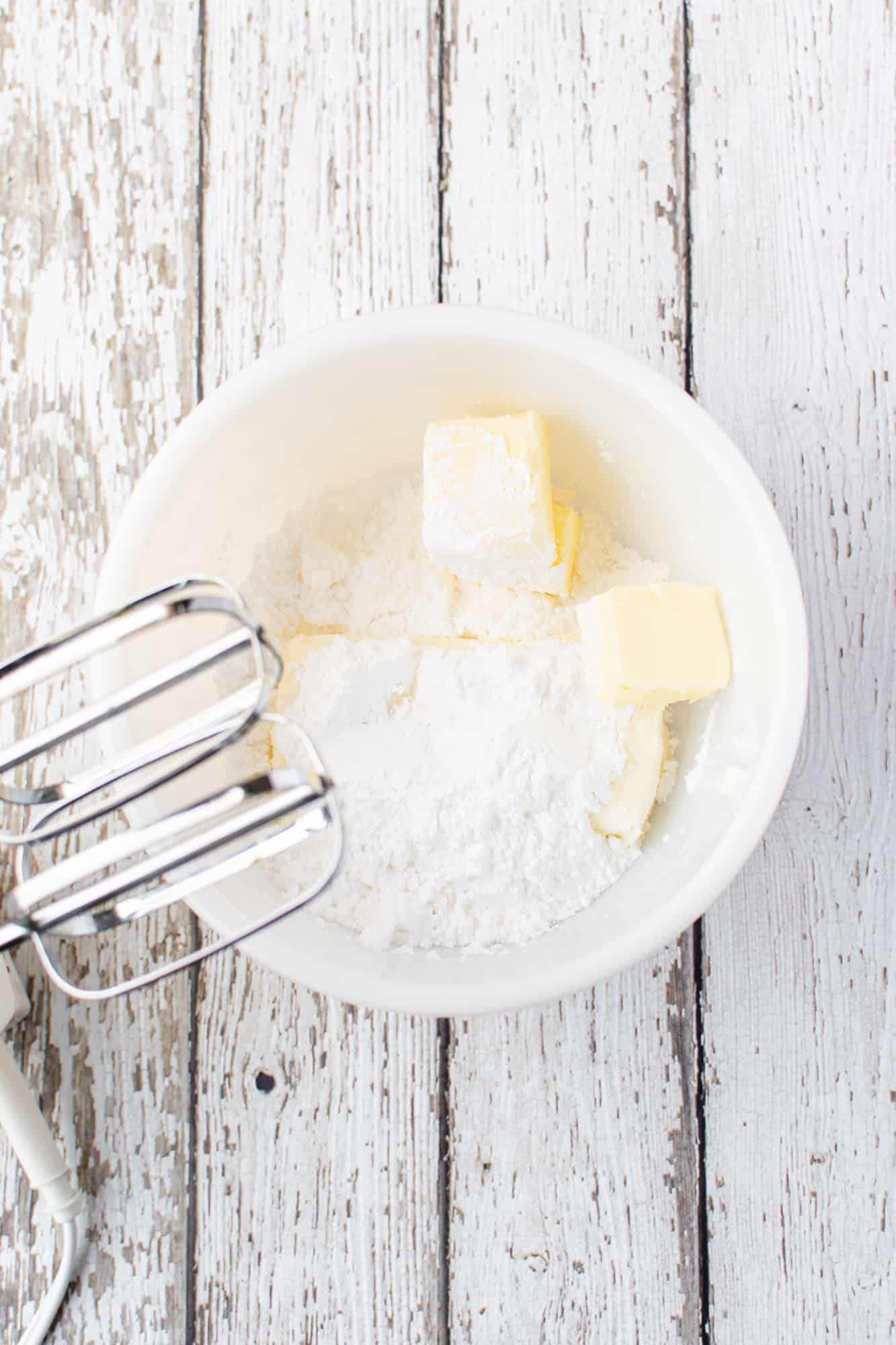 softened cream cheese and softened butter mixed together with an electric mixer in a white bowl.