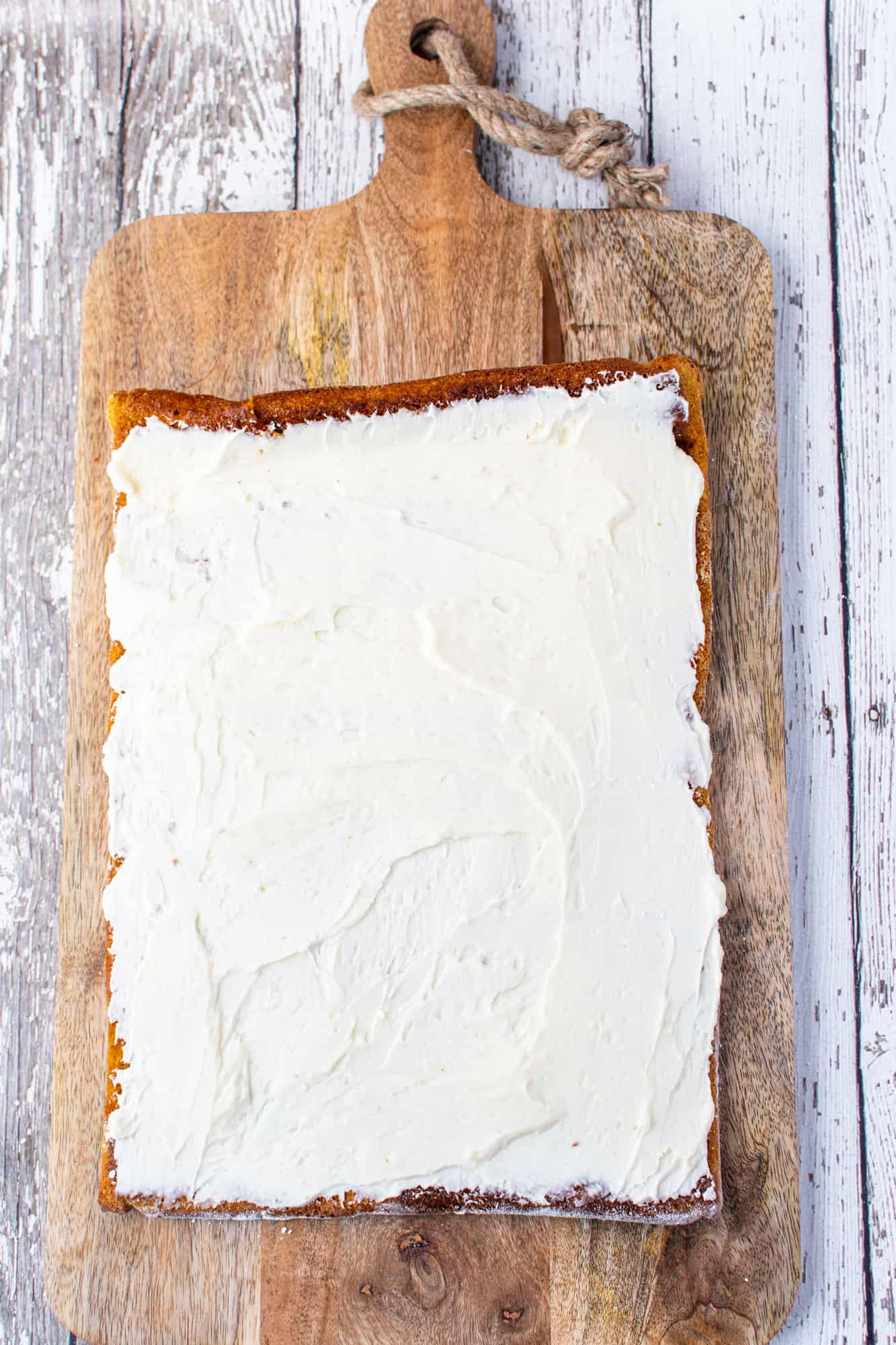 sweetened cream cheese filling spread onto the pumpkin cake.