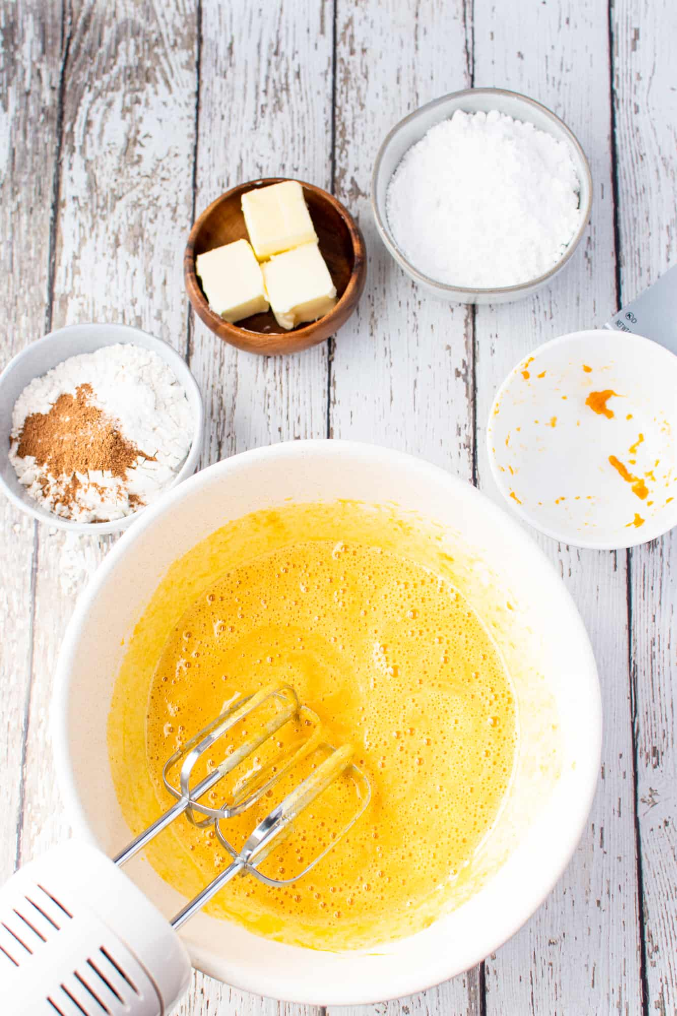 pure pumpkin and vanilla extract added to sugar and egg mixture in a white mixing bowl.