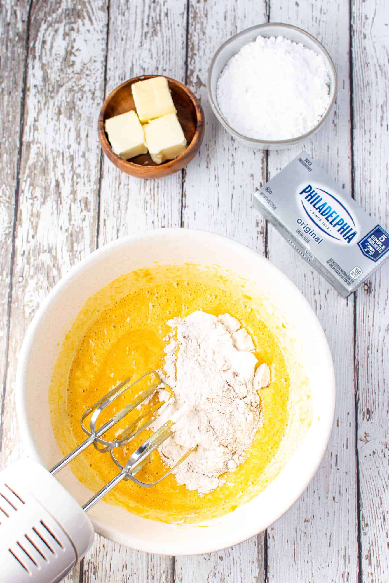 flour mixture added to the pumpkin egg mixture in a bowl.
