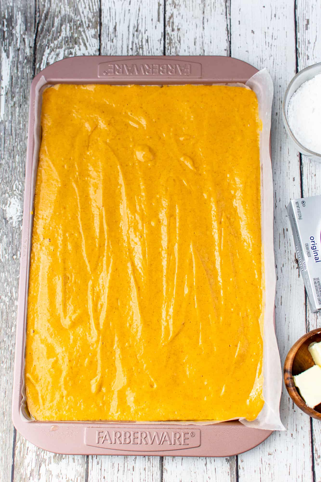 pumpkin cake batter spread into a jelly roll cake pan.