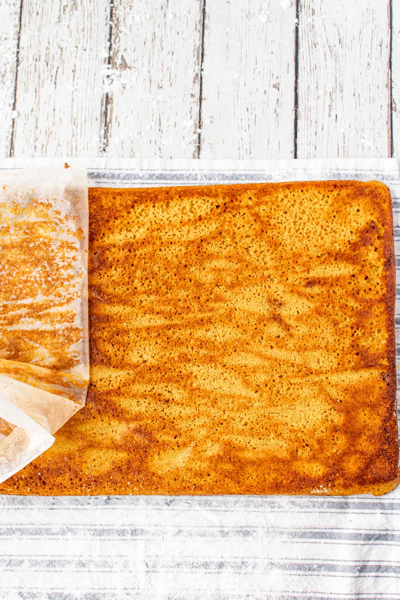 unrolled pumpkin cake and parchment paper being peeled off.