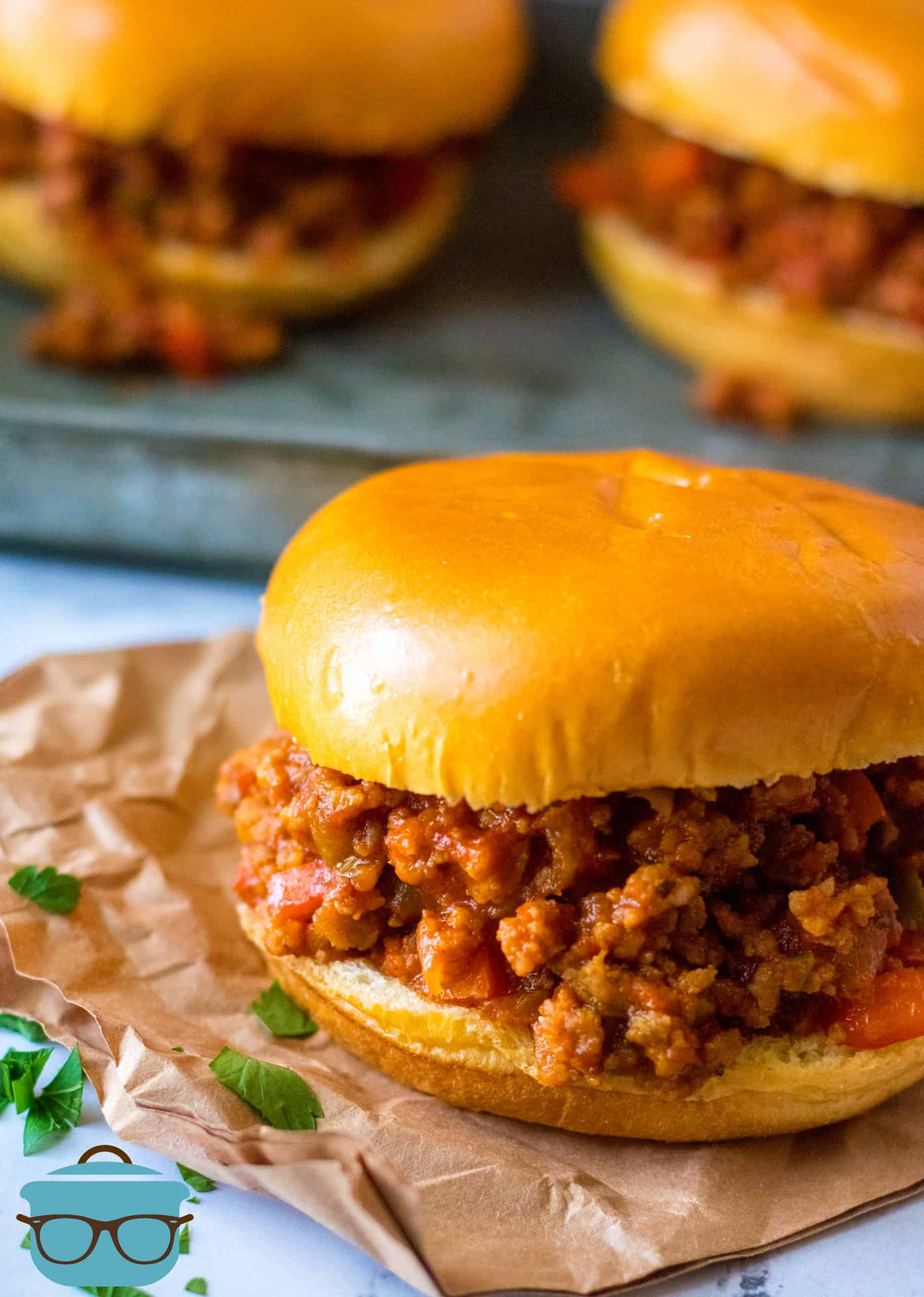 Sausage and Peppers Italian Sloppy Joes shown served on Brioche Buns and placed on a brown napkin.