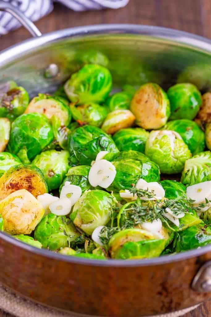 sliced brussel sprouts, garlic and thyme added to a large pan