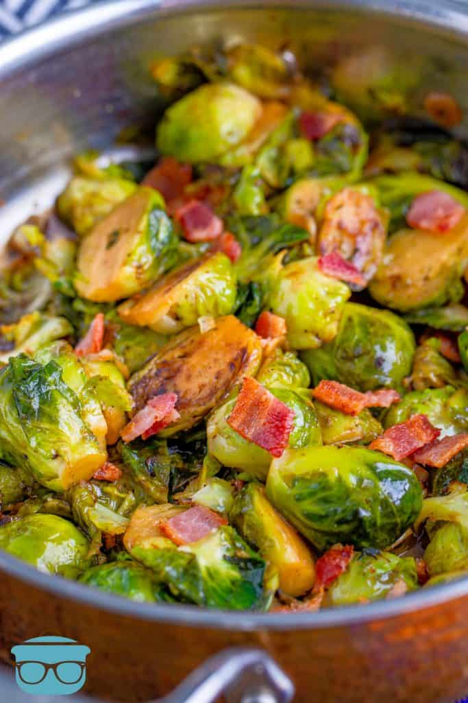 cooked sliced brussel sprouts in a large copper ban sprinkled with chopped bacon