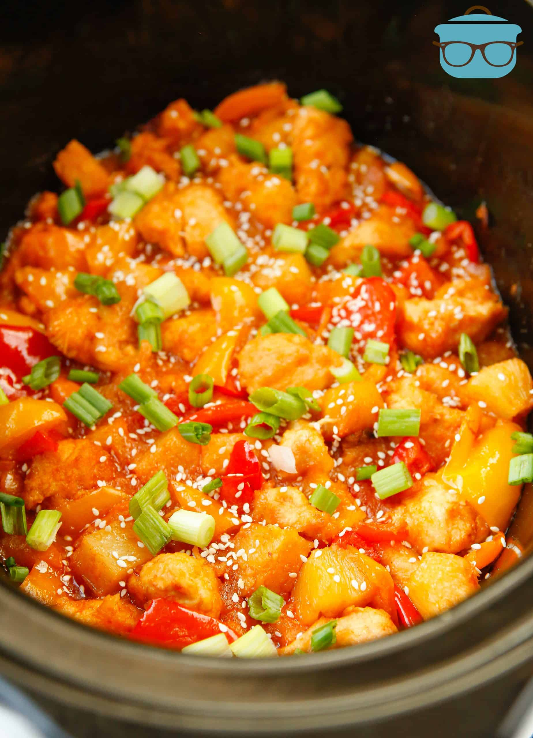 Sweet & Sour Chicken, fully cooked, down in a black oval slow cooker.