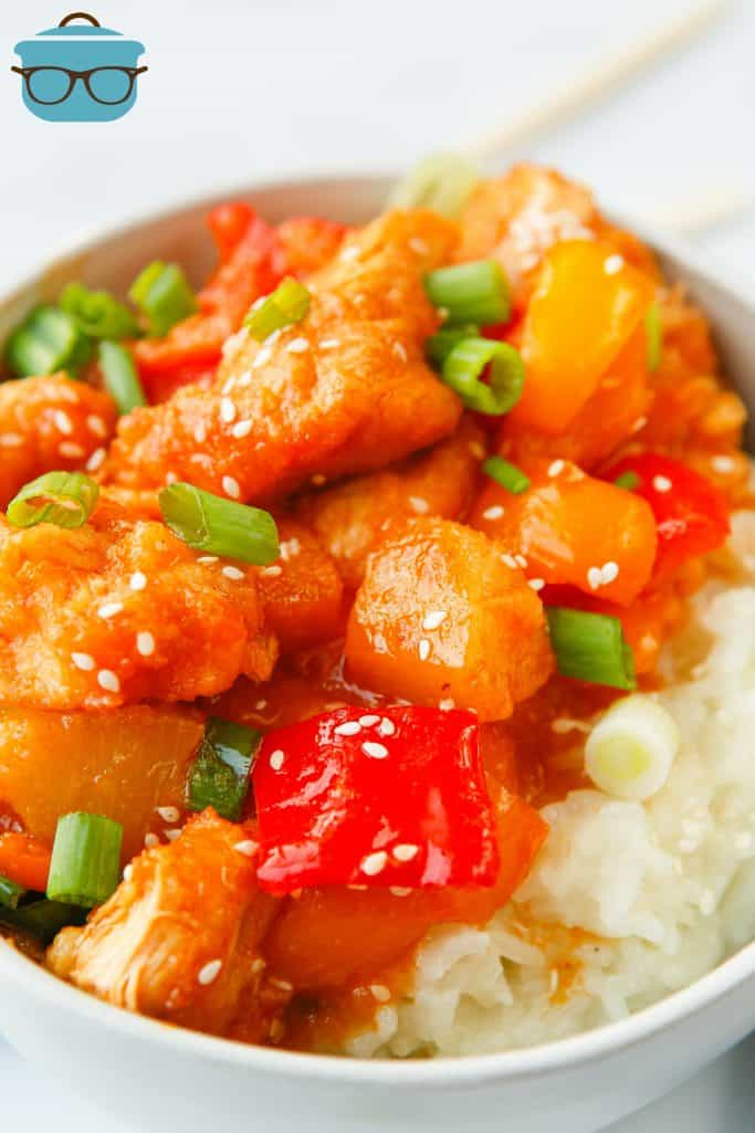sweet and sour chicken served over rice in a bowl with chopsticks