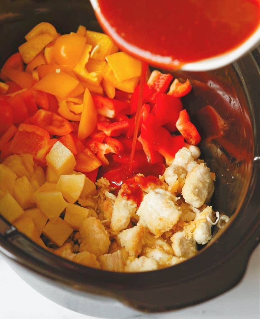 sweet and sour sauce poured over chicken and bell peppers in a slow cooker