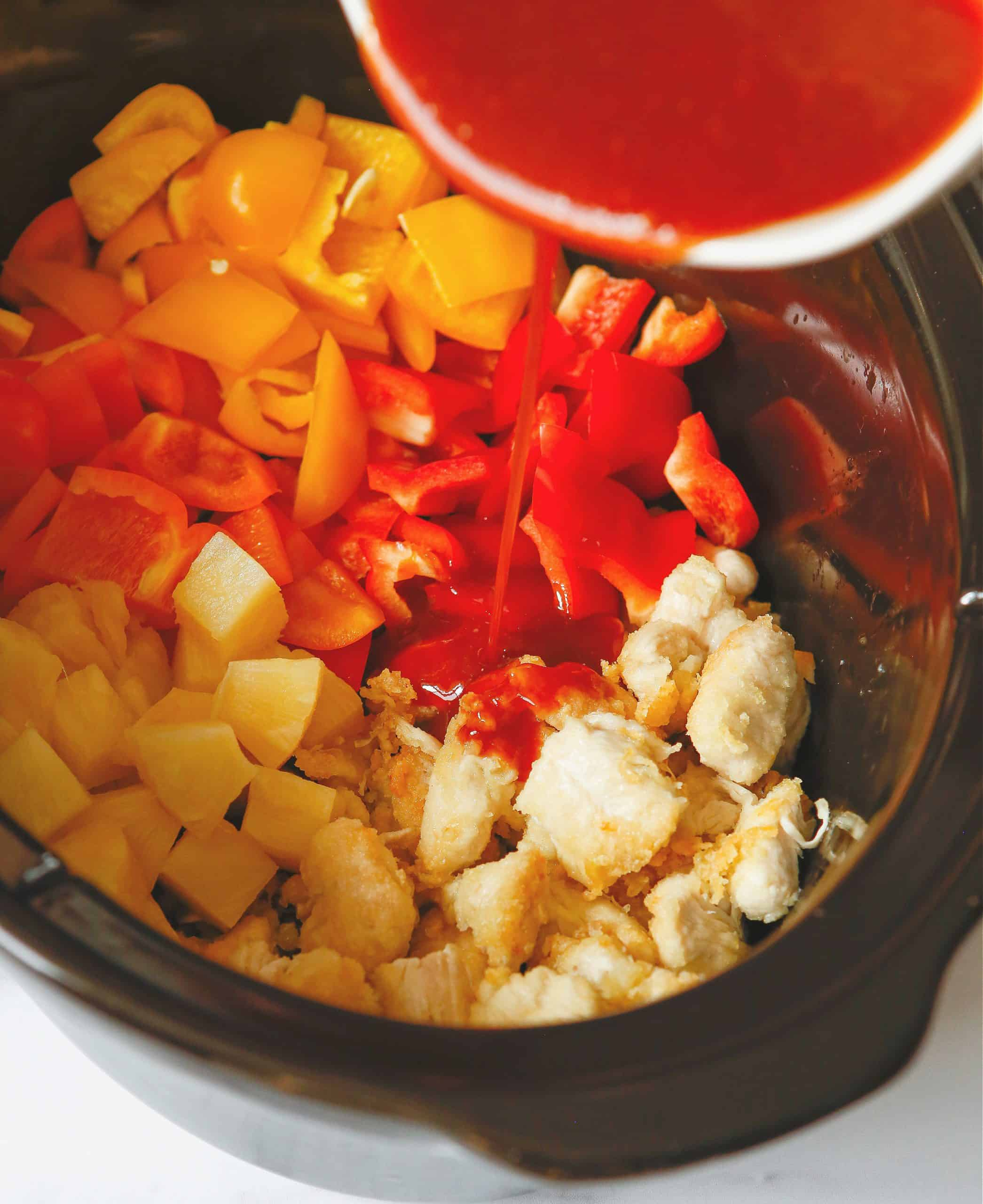 sweet and sour sauce poured over chicken and bell peppers in a slow cooker.