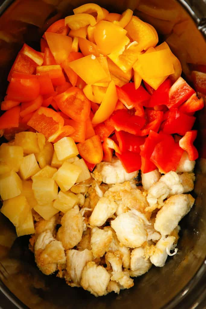 diced fried chicken, diced bell peppers and pineapple chunks in the bottom of an oval slow cooker