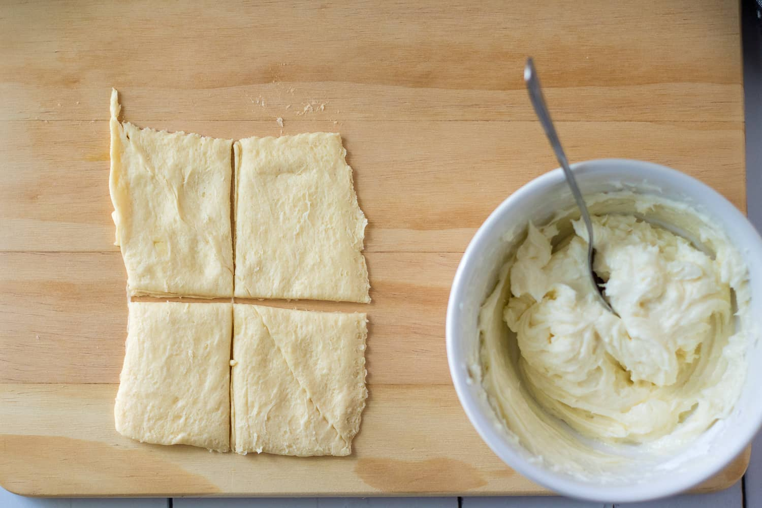 crescent roll dough made into four squares with a bowl of sweetened cream cheese off to the right side.