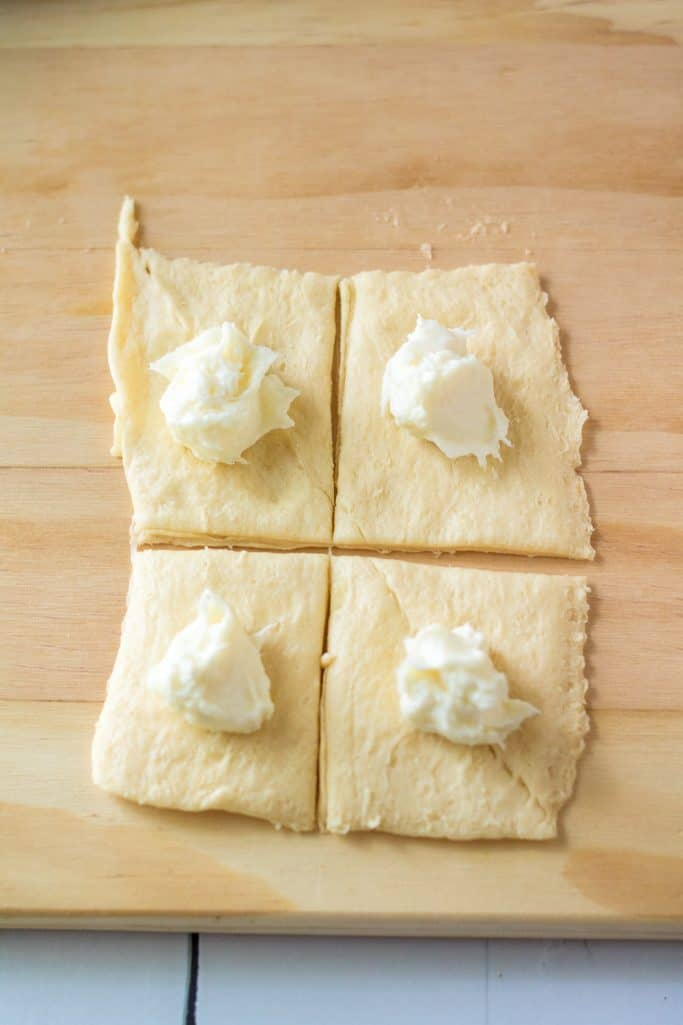 cream cheese filling scooped into crescent roll dough squares