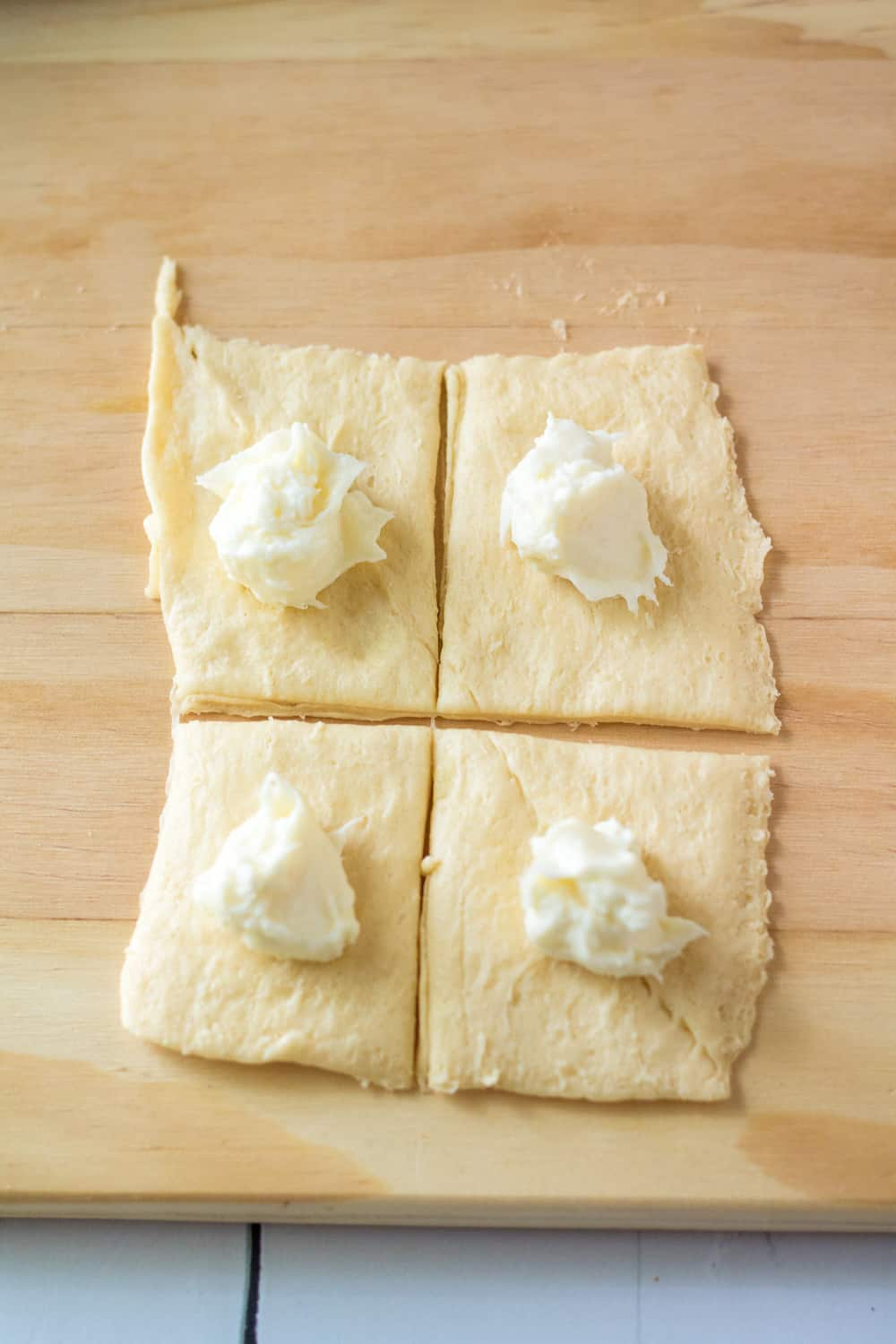 cream cheese filling scooped into crescent roll dough squares.