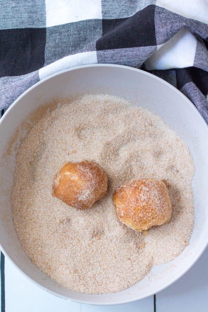 rolling air fried dough balls in pumpkin spice and cinnamon sugar mixture in a white bowl
