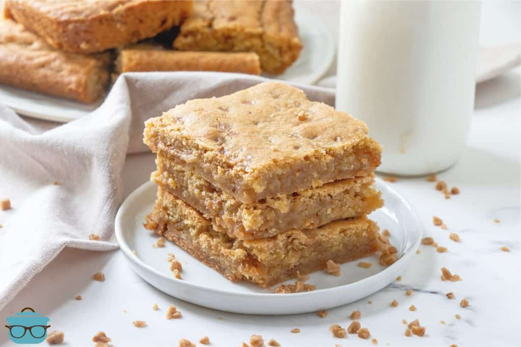 Homemade Butter Rum Toffee Blondies, shown with three slices on a white plate and a bottle of milk in the background