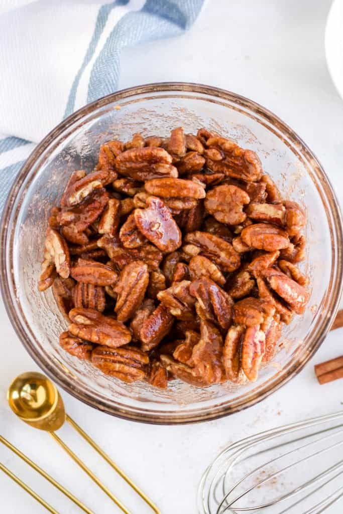 fully coated and seasoned pecan halves in a clear bowl