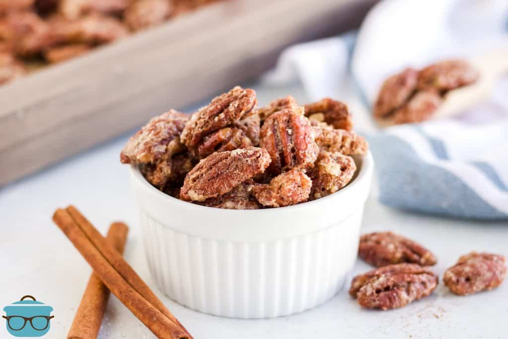 candied pecans shown in a small white ramekin bowl with cinnamon sticks on the side