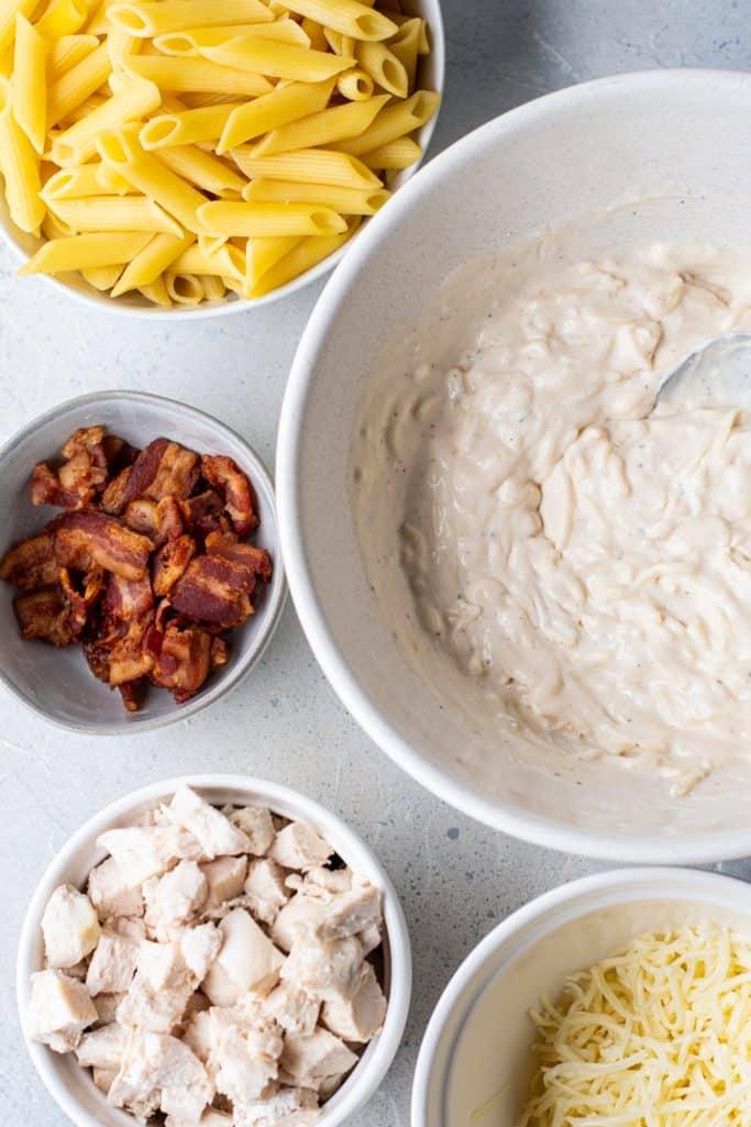 creme de leite, mistura de molho de rancho, alho, pimenta, molho Alfredo, queijo mussarela misturado em uma tigela branca