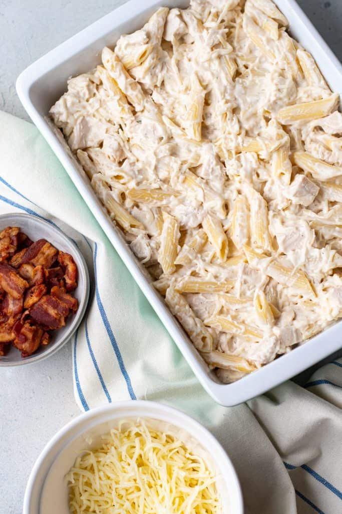 cooked penne pasta, cooked chopped chicken mixed together with cream sauce in a rectangle baking dish
