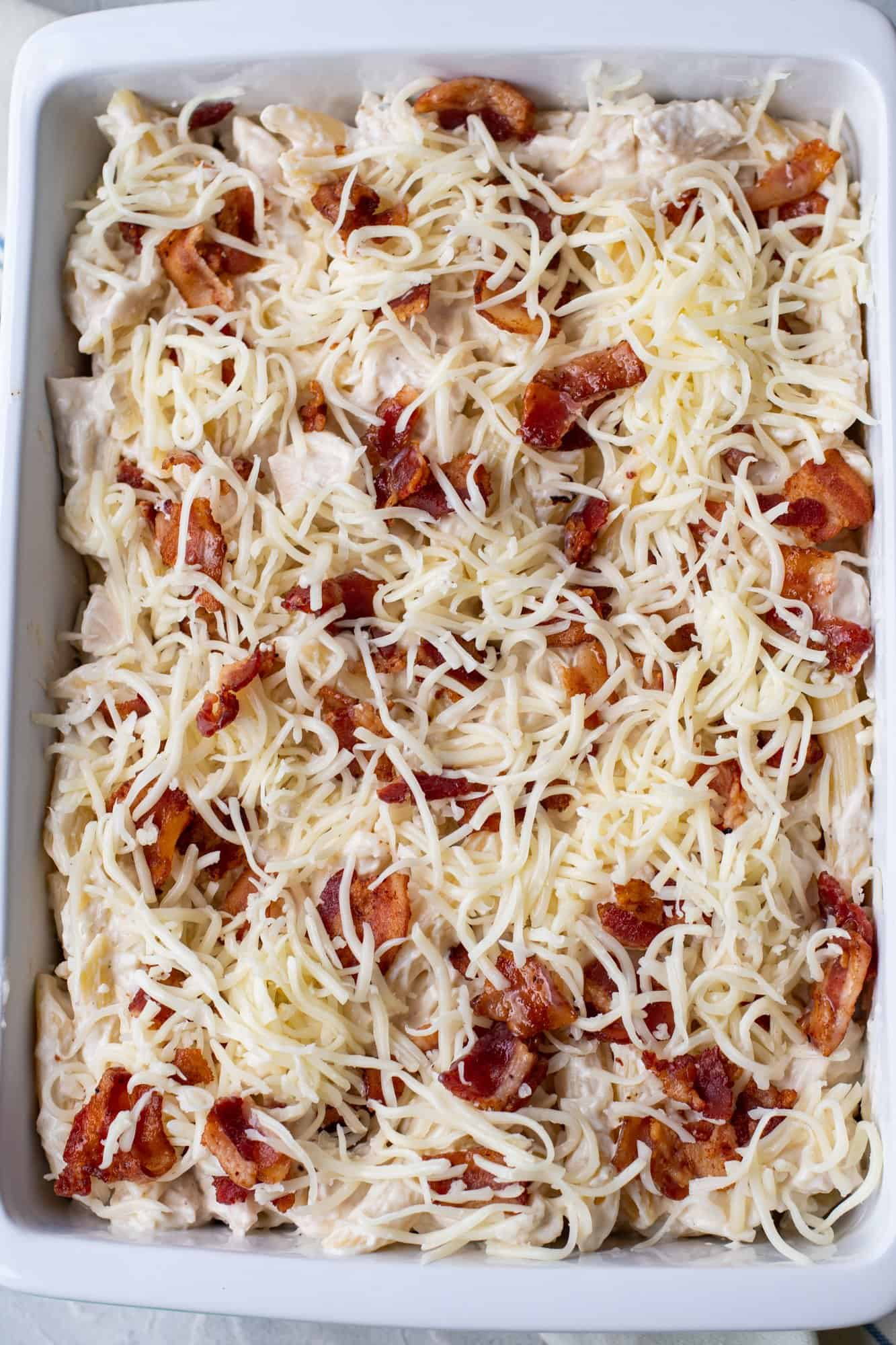 shredded cheese and cooked bacon sprinkled on top of pasta in baking dish
