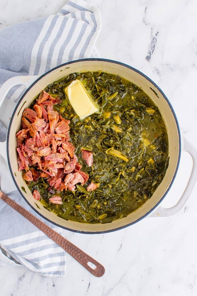 shredded ham added cooked collard greens and butter in a a white pot with a copper spoon on the side