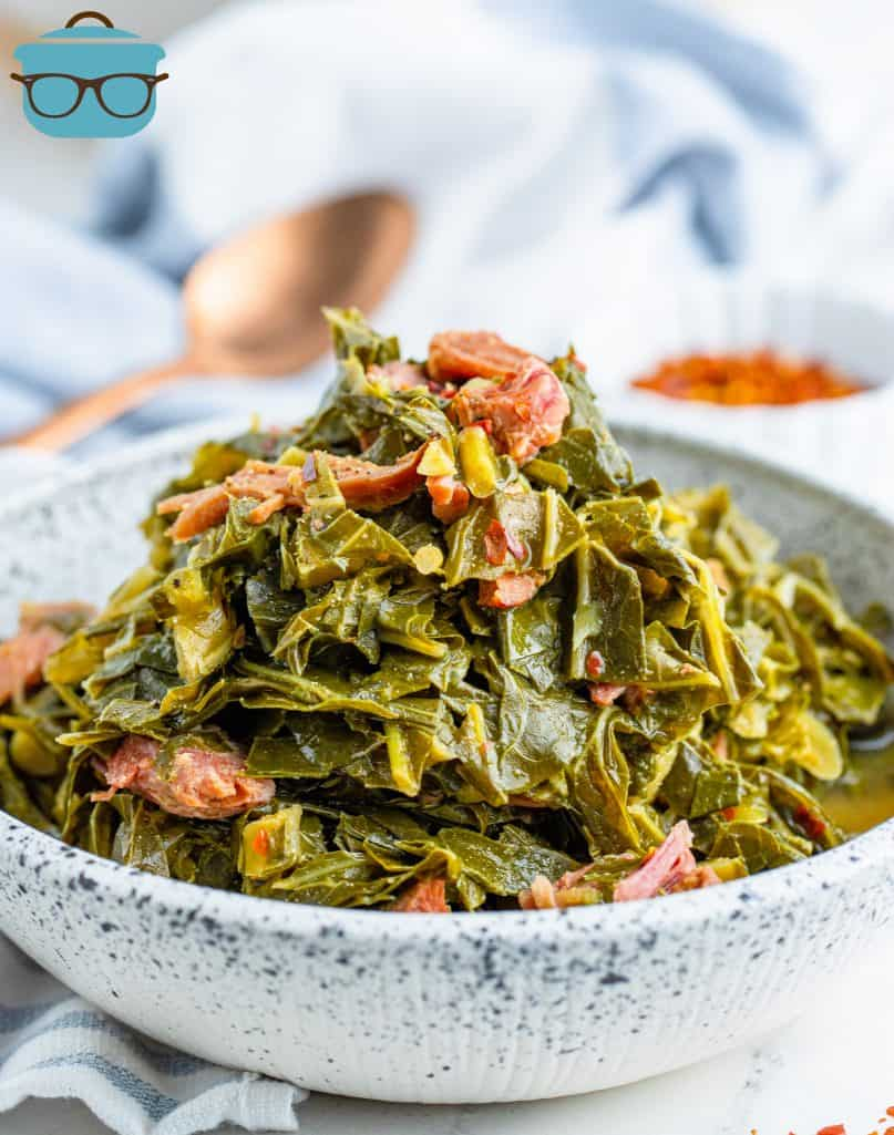 cooked collard greens and ham in a bowl with a copper spoon in the background