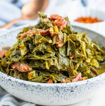 Collard Greens with ham in a speckled white and blue bowls with a copper spoon in the background