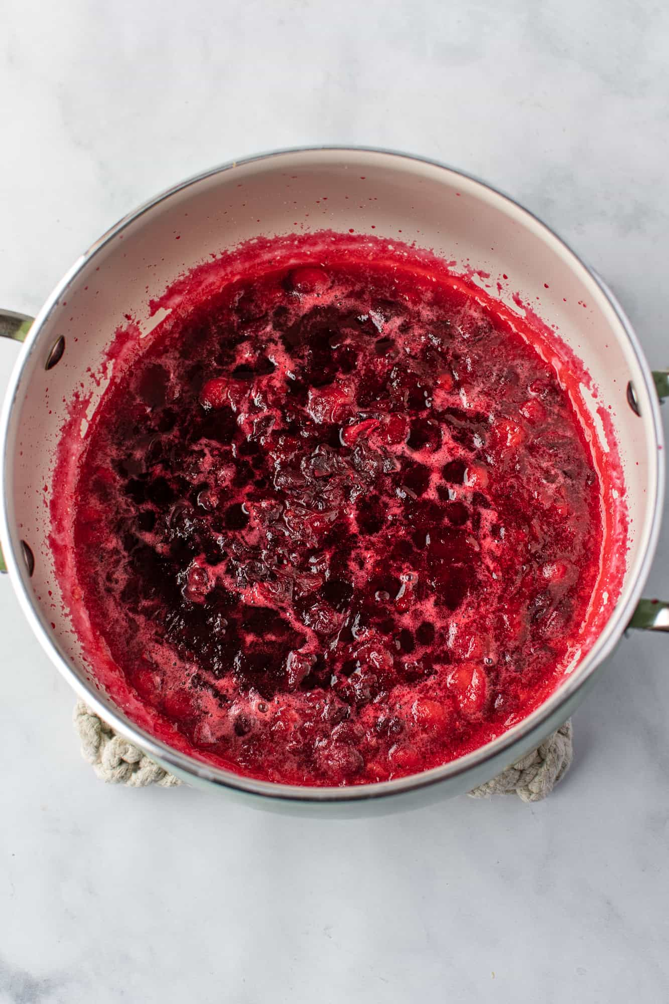 crushed cranberries in a silver sauce pan.