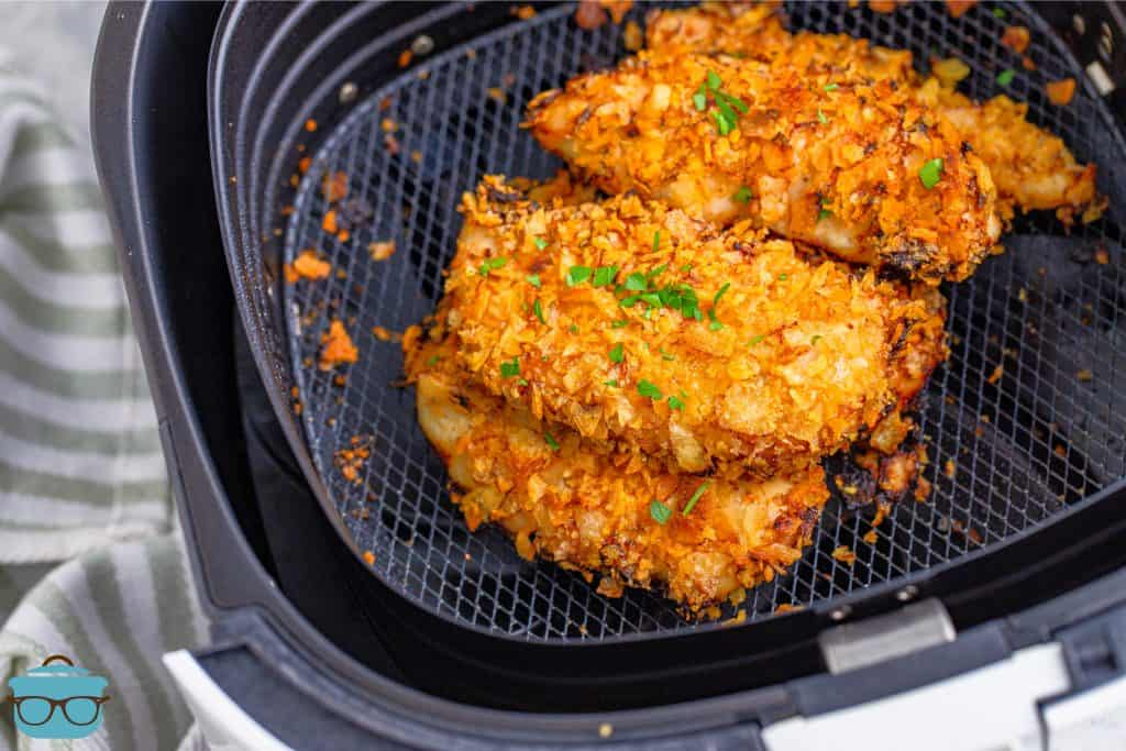 Crispy, fully cooked chicken tenders shown in the bottom of an air fryer basket