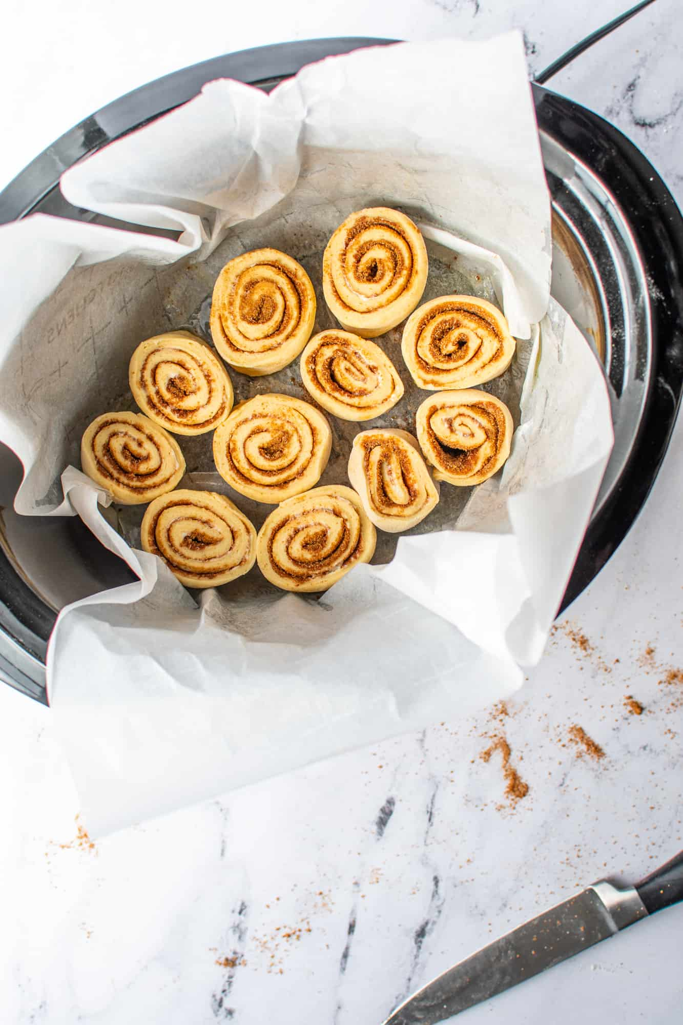sliced cinnamon rolls layered into the bottom of an oval crock pot lined with parchment paper