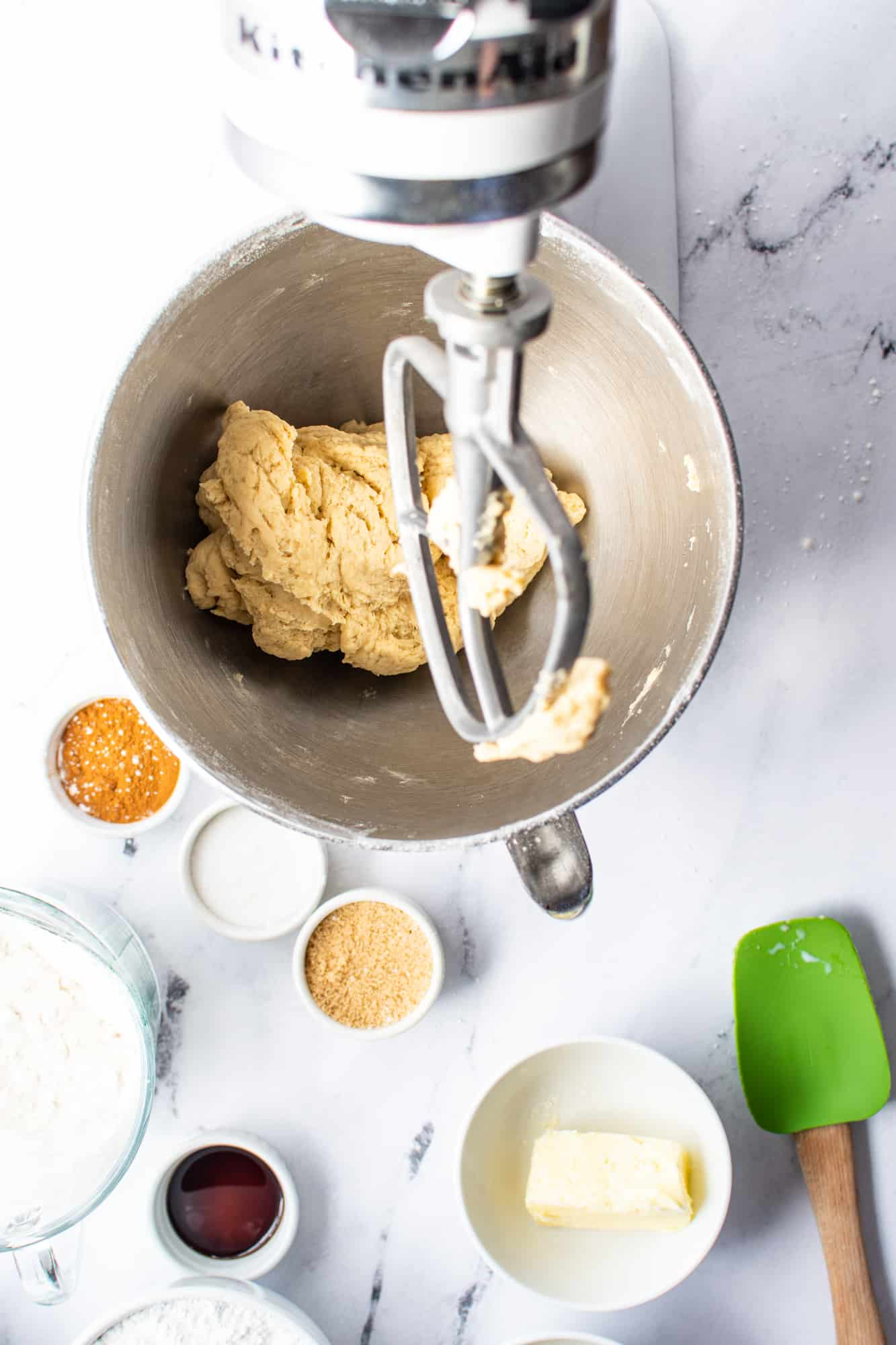 thick cinnamon dough batter almost formed into a bowl in a stand mixer