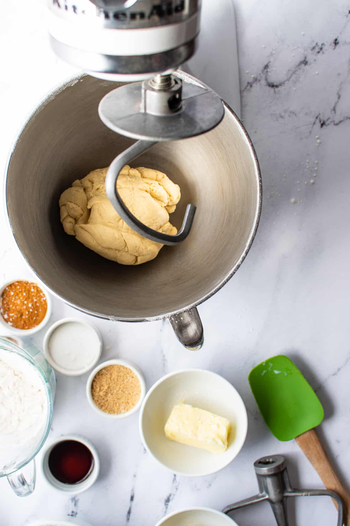 dough hook attached to stand mixer with cinnamon roll dough ball in the bottom of the stand mixer bowl