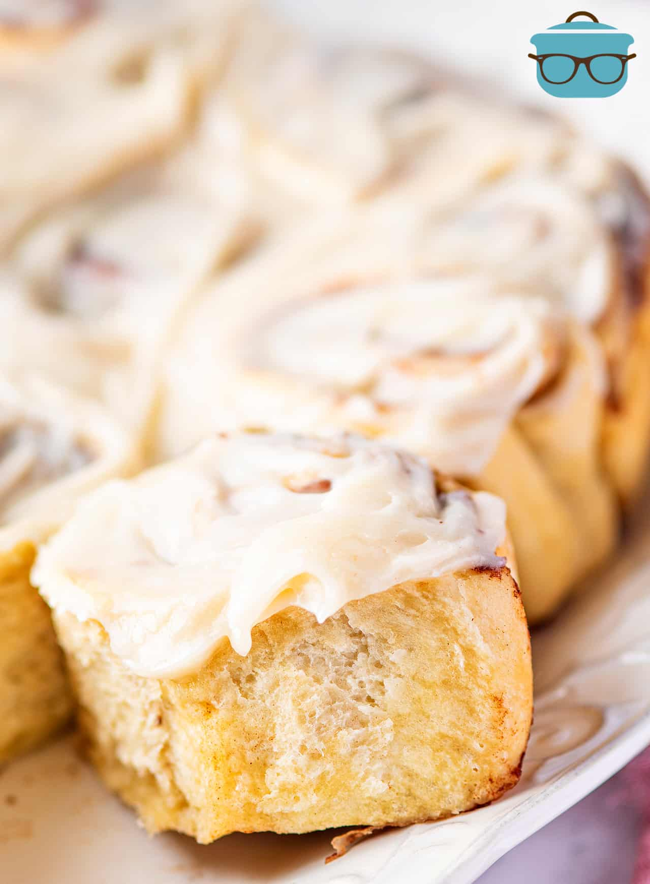 close up shot of cinnamon roll topped with cream cheese frosting on a white plate