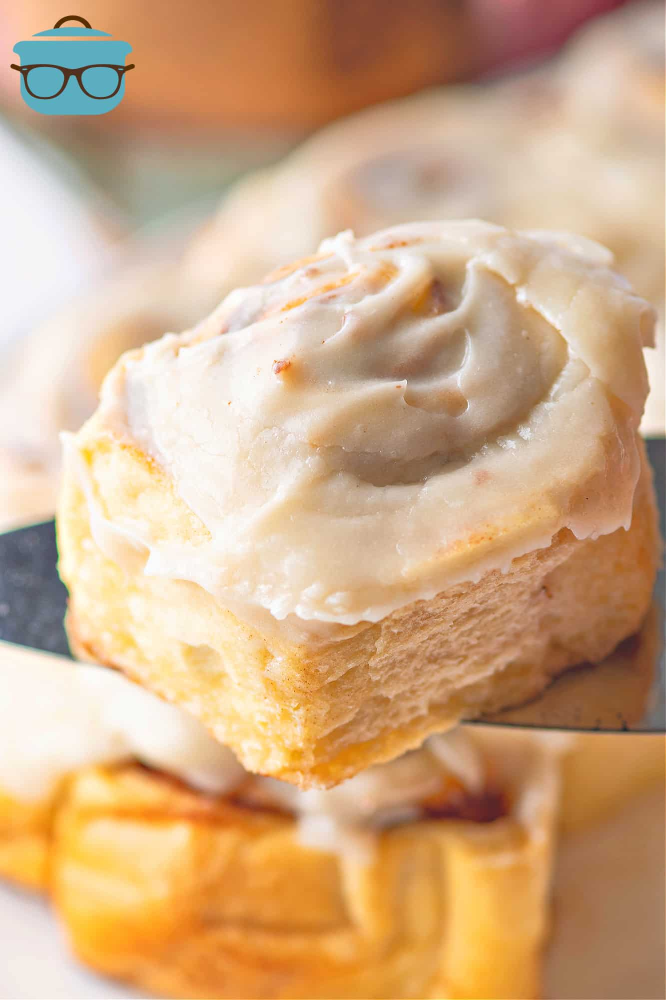 Crock Pot Cinnamon Rolls with maple cream cheese frosting, one roll on a spatula