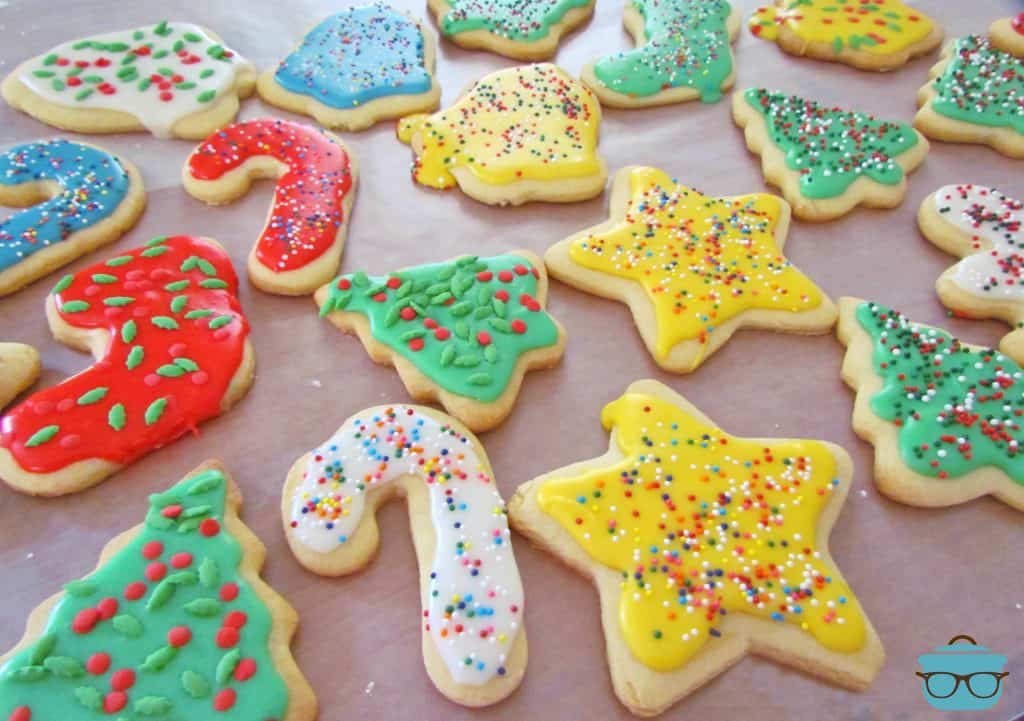 Cut-Out Sugar Cookies with yellow, blue, white and green icing with sprinkles on a sheet of wax paper