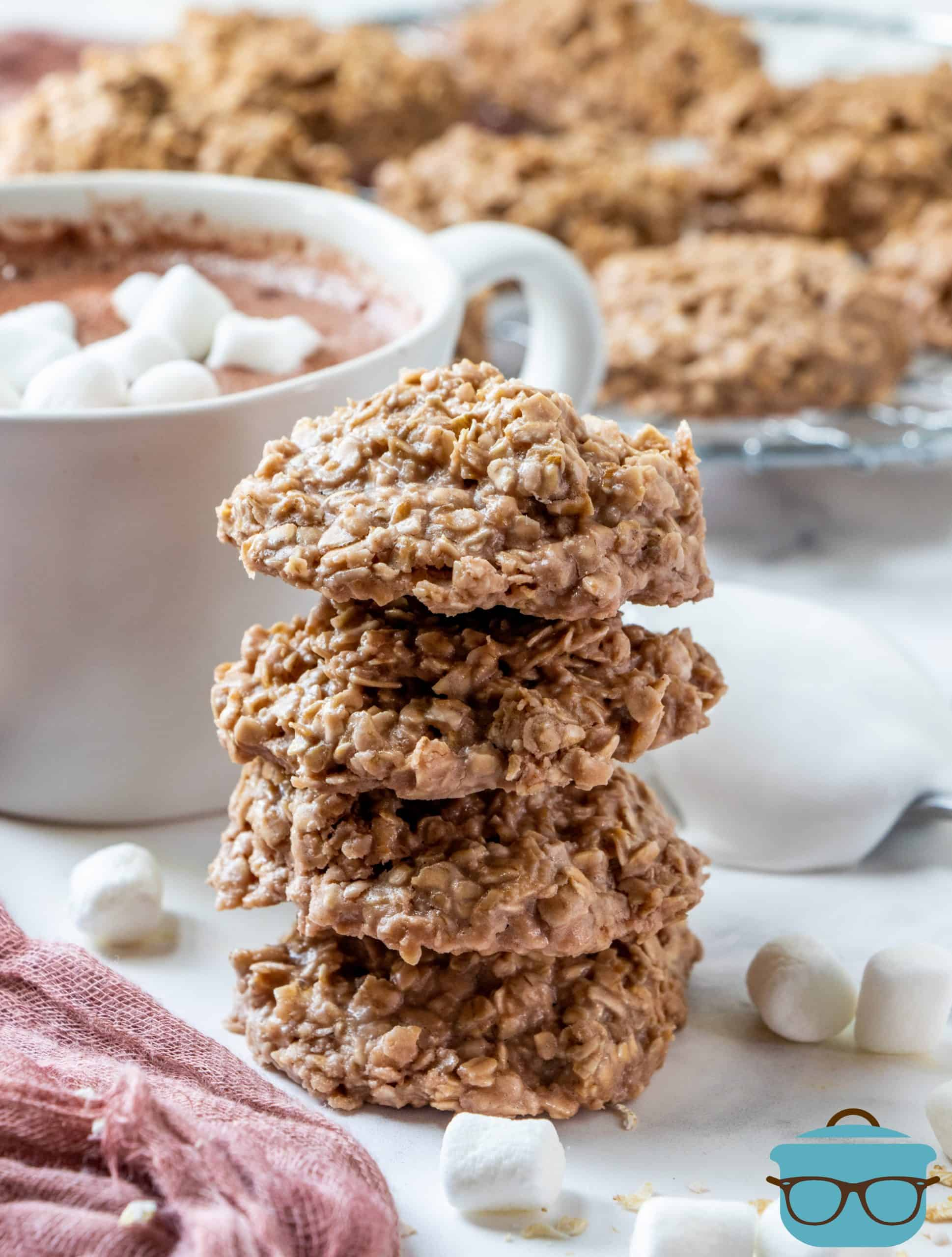 HOT CHOCOLATE NO BAKE COOKIES, stacked with a cup of hot chocolate in the background.