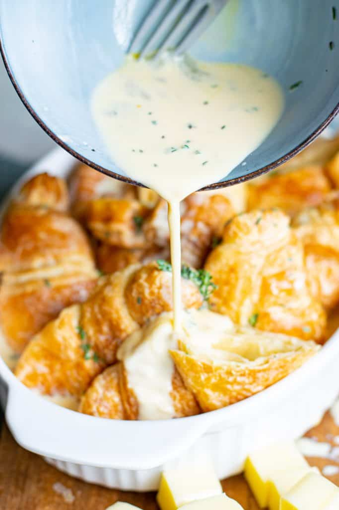 pour egg and cream mixture over croissants in a white oval baking dish