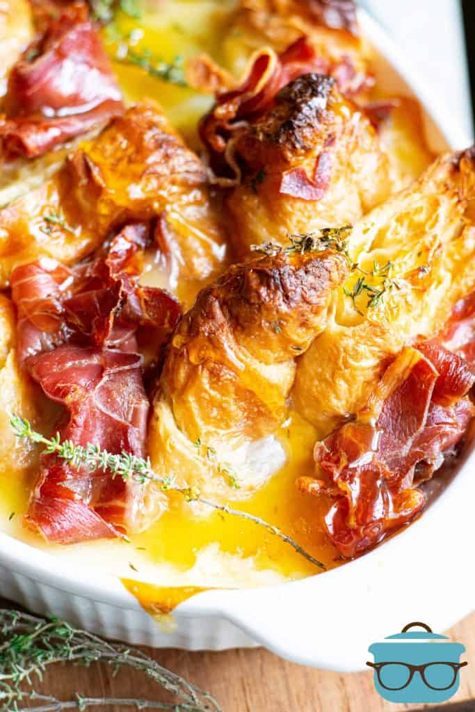 close up photo of cooked ham and croissants in an egg and cream mixture with a sprig of fresh thyme on top