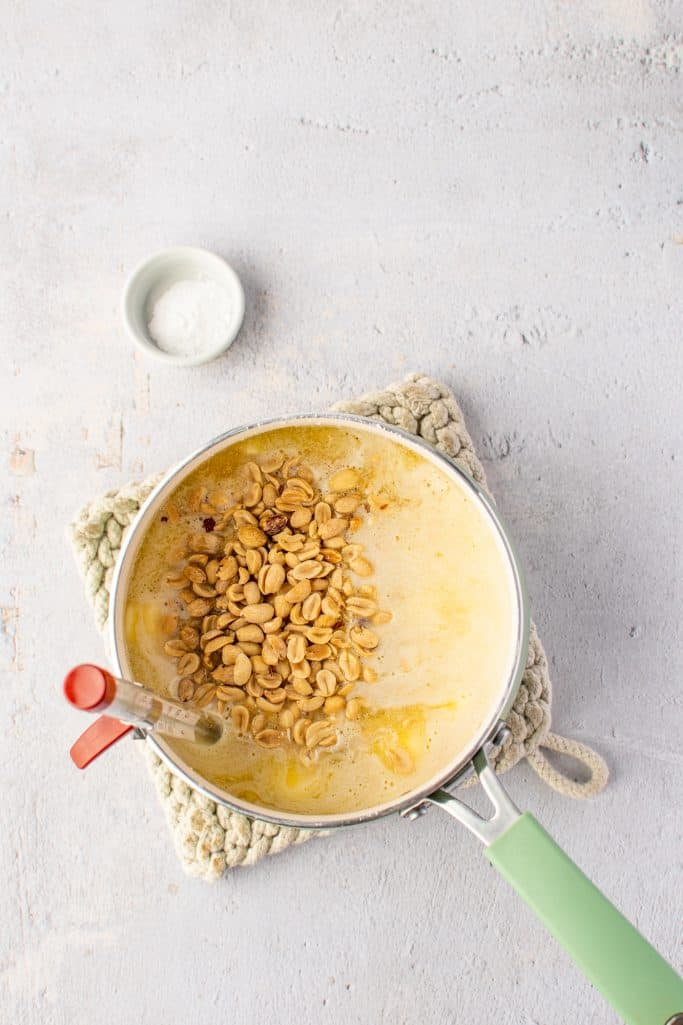 peanuts added to boiling liquid candy mixture in a sauce pan