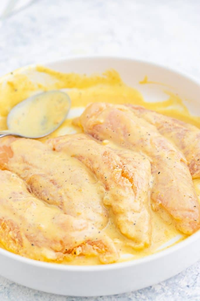 fully coated chicken tenderloins in honey mustard sauce in a white bowl