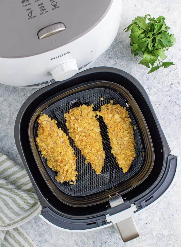 raw, coated chicken tenders in the bottom of a black air fryer basket