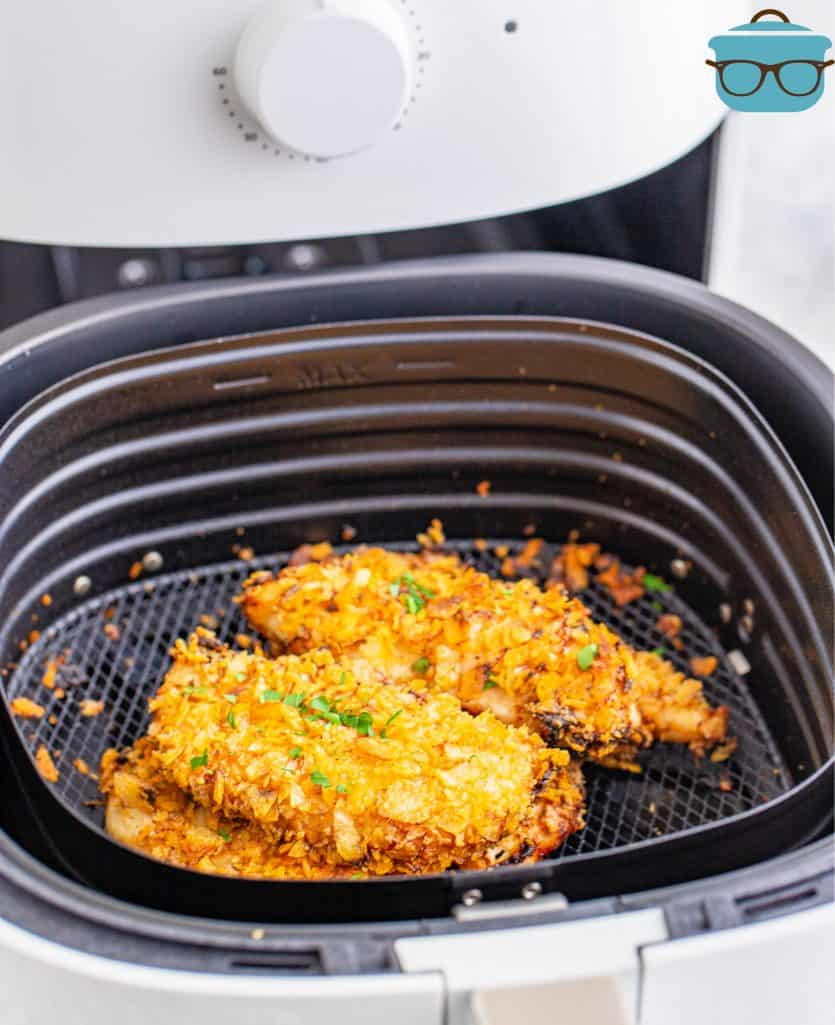 Fully cooked air fryer potato chip coated chicken tenders in an air fryer basket