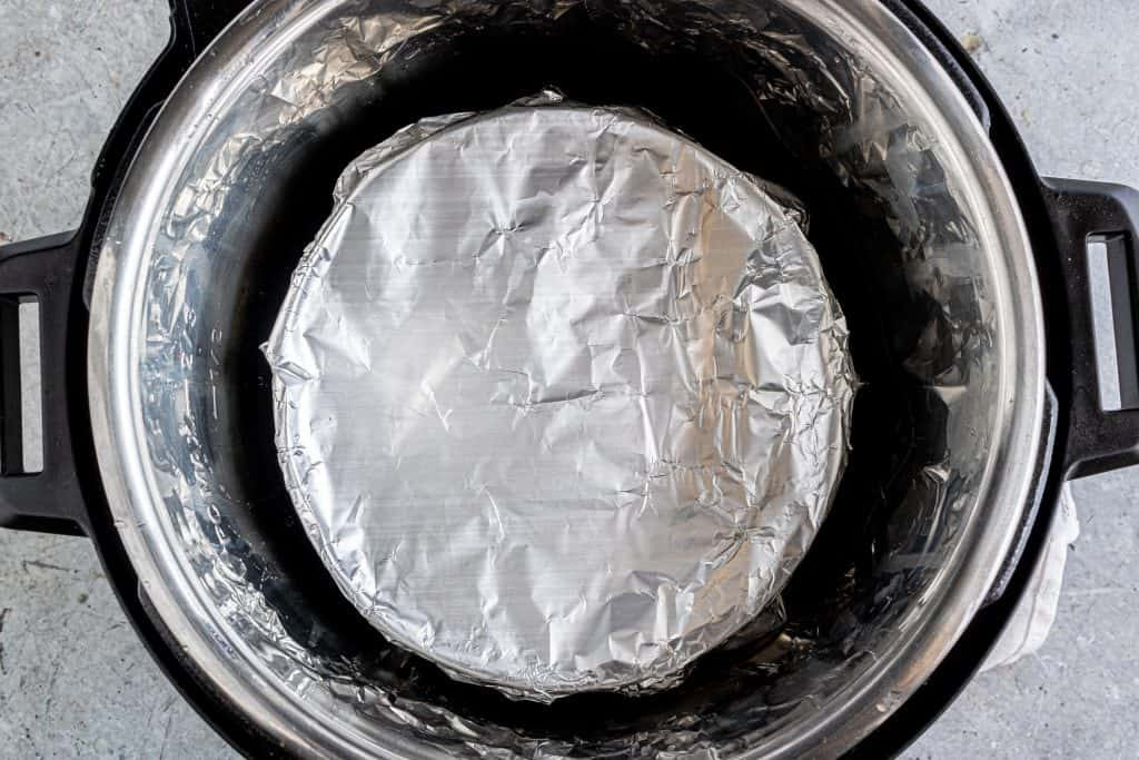 aluminum foil covered pan inside an electric pressure cooker
