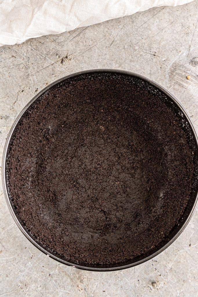Oreo cookie crumbs pressed into the bottom of a 7-inch springform pan
